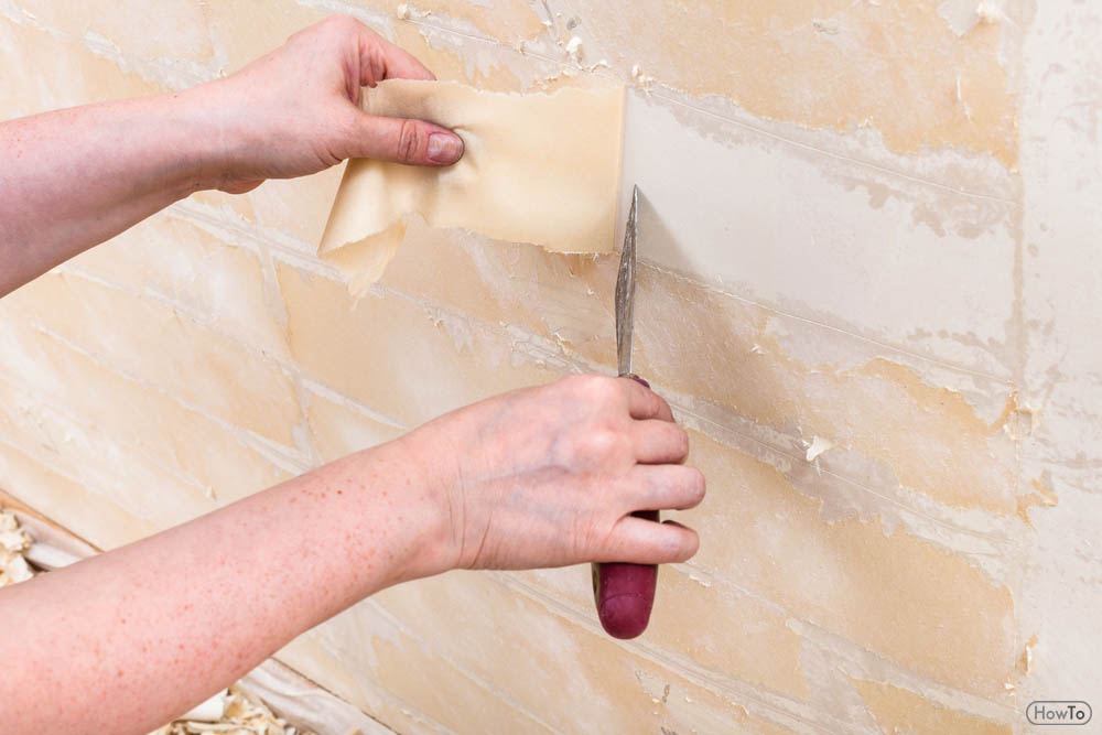 You can either use the scoring tool or sandpaper to create holes on the wallpaper. The holes on the wallpaper will allow the removing solution to penetrate ...